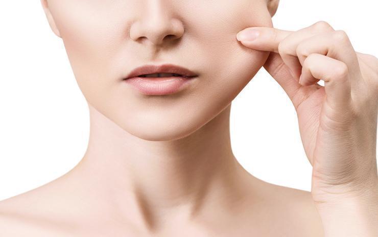 Žena testira elastičnost kože lica