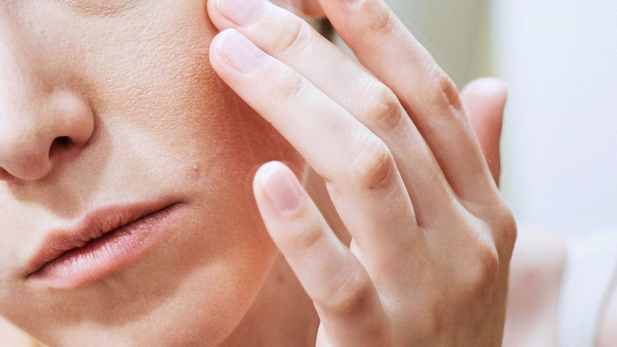 Osoba dodiruje kožu lica sa ekcemom